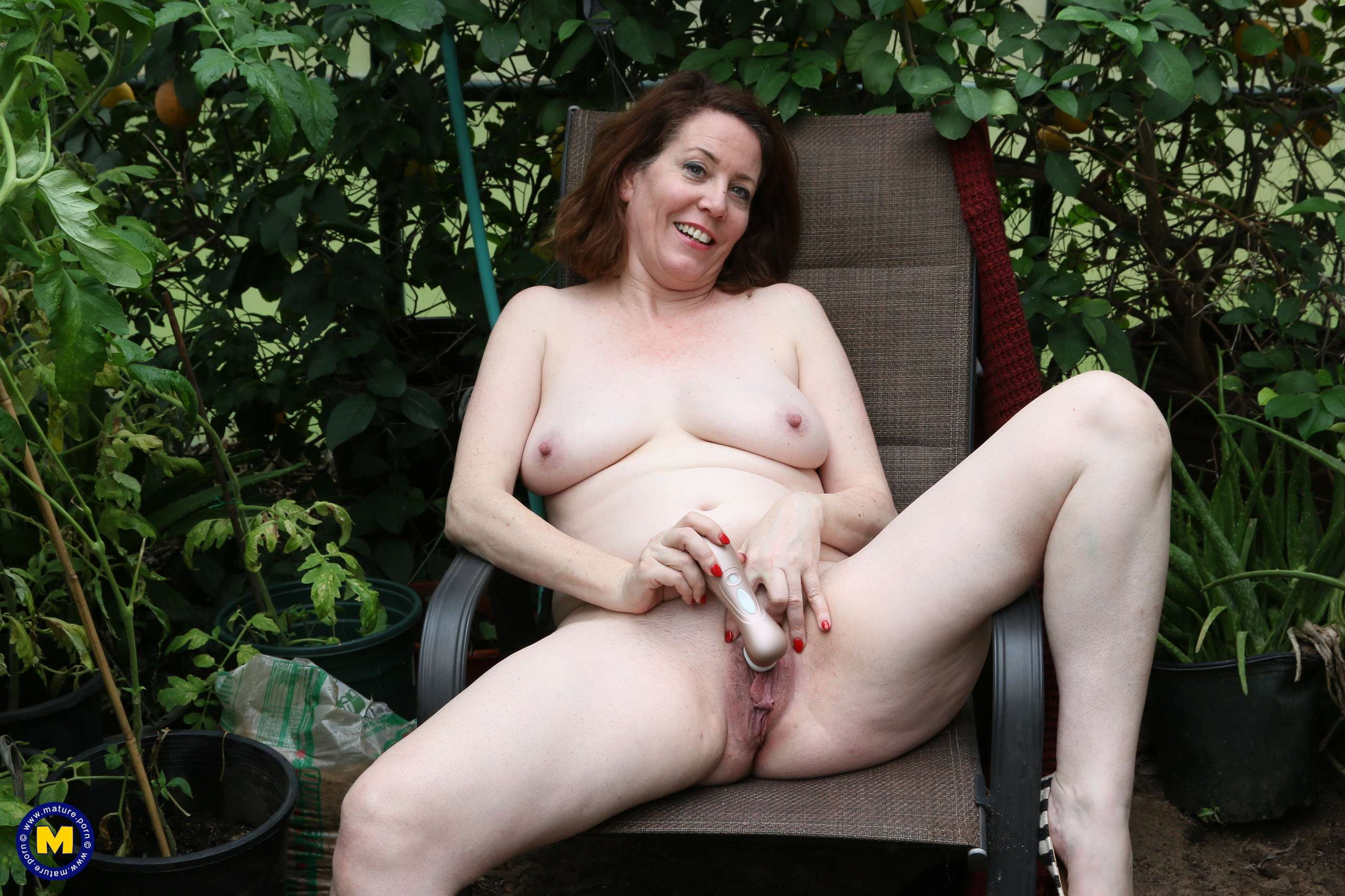 Naughty American MILF fooling around in the garden without panties