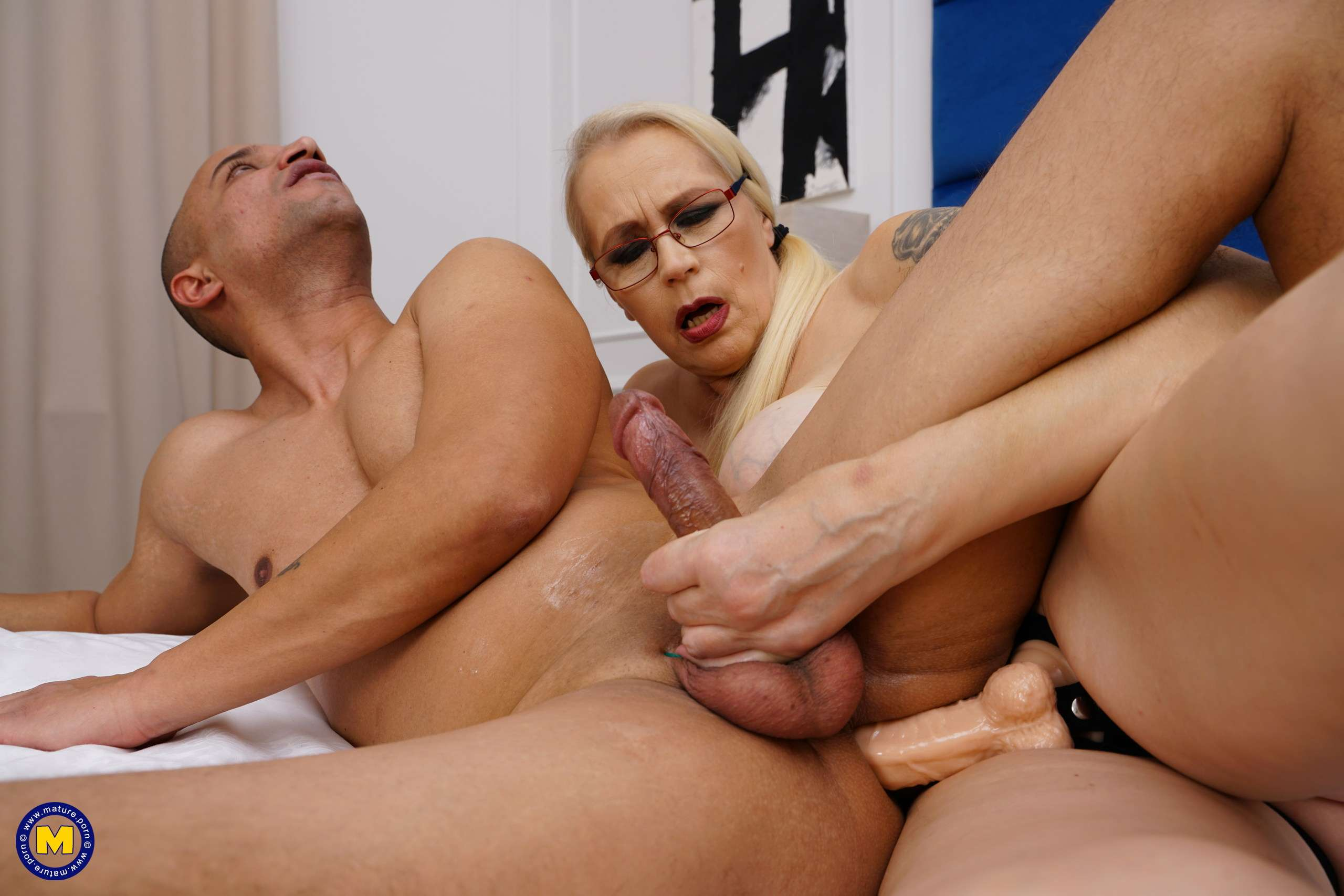 Dominant mature slut fucking a guy with a strapon dildo
